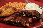 stock photo of baby back ribs  - Barbecued baby back ribs and chicken with coleslaw and baked beans closeup - JPG