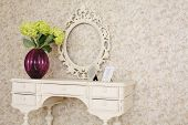 stock photo of console-mirror  - Wooden carved dressing table with blank frame and flowers in light room - JPG