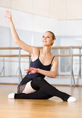 stock photo of ballet barre  - Ballet dancer works out sitting on the floor in the classroom with barre and mirrors - JPG