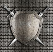 stock photo of crossed swords  - Shield and two swords crossed hanging on metal wall with rivets - JPG