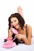 Sexy woman with pink phone on bed at home