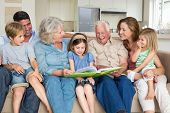 stock photo of storybook  - Multigeneration family reading storybook in living room - JPG