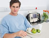 Portrait of handsome man having meal on hospital bed