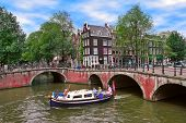AMSTERDAM, NETHERLANDS - JULY16, 2007: Boat on canal passing by bridges and houses. Small boat trips