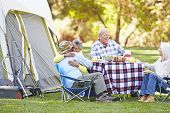 Two Senior Couples Enjoying Camping Holiday In Countryside