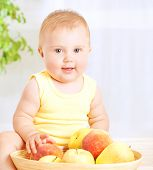 Happy little baby girl eating fresh tasty fruits for lunch, enjoying healthy food at home, organic n