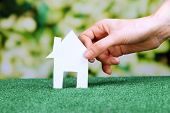 Little paper house in hand on green grass on bright background