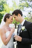 Romantic bride and groom holding champagne flutes in park