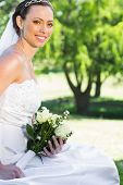 Portrait of beautiful bride holding flower bouquet while sitting in garden