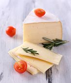 Tasty Camembert cheese with tomato and rosemary, on wooden table