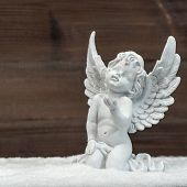 picture of guardian  - little white guardian angel in snow over rustic wooden background. vintage style christmas decoration