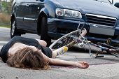 picture of accident emergency  - Unconscious female cyclist lying on street after road accident - JPG