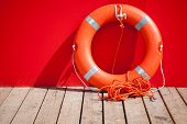 stock photo of lifeguard  - Lifebuoy stands on wooden floor nearby red wall of lifeguard station - JPG