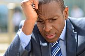 pic of forehead  - Businessman in depression with hand on forehead - JPG