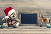 picture of wooden horse  - nostalgic christmas decoration with antique toys teddy bear and wooden rocking horse. vintage style picture with blackboard for your text