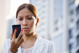 pic of disappointed  - Businesswoman with disappointed expression using mobile phone in city street receiving bad news via email  - JPG