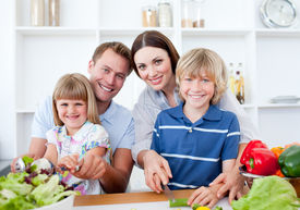stock photo of healthy eating girl  - Happy Family Preparing Dinner Together In A Kitchen - JPG