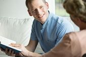 stock photo of ward  - Cheerful young male caregiver sitting with his older ward - JPG