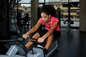 image of afro  - Attractive afro american woman with curly hair working out at gym doing legs exercise on press machine - JPG