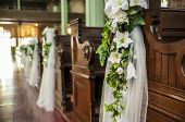 picture of bench  - Wedding decoration white flowers and green leafs hanging on the church benches - JPG