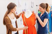 stock photo of dress mannequin  - Two beautiful female designers measuring dress on the mannequin - JPG