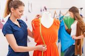 picture of dress mannequin  - Beautiful female fashion designer measuring dress on the mannequin while her colleague standing on background - JPG