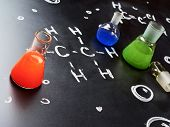 foto of liquids  - Chemistry glass tubes and vessels filled with colorful liquids over the blackboard - JPG