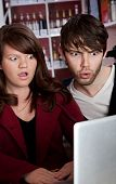 stock photo of smut  - Woman and man staring in disbelief at a laptop - JPG