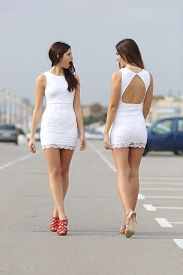 picture of hate  - Two women walking on the street with the same dress looking each other with hate - JPG