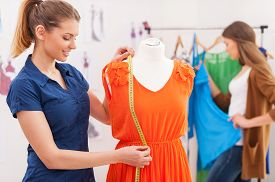 stock photo of dress mannequin  - Beautiful female fashion designer measuring dress on the mannequin while her colleague standing on background - JPG