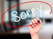 stock photo of forgiven  - Man Hand writing Sorry with marker on transparent wipe board - JPG