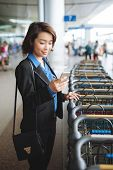 stock photo of trolley  - Business woman standing near a row of luggage trolleys and dialing a number - JPG
