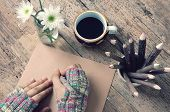 picture of sad christmas  - Women hand wear wool gloves in wintertime writting letter for lover from distant lonely background in cold day of christmas season hot coffee cup flower pot pencil on wooden background - JPG