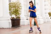 foto of inline skating  - Beautiful girl skating in the city and listening to music from her smartphone - JPG