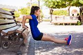 picture of dipping  - Profile view of a female athlete doing some tricep dips on a park bench - JPG