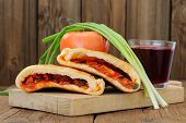 stock photo of scallion  - Two pieces of pizza calzone with glass of red wine fresh scallion and tomato on wooden board horizontal - JPG