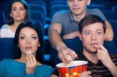 picture of popcorn  - Excited young couple eating popcorn and watching movie at the cinema while man from the back seat stealing their popcorn - JPG
