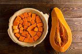 stock photo of pumpkin pie  - Raw pumpkin pie on the brown wooden background  - JPG