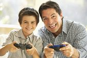 stock photo of indoor games  - Father And Son Playing Video Game At Home - JPG