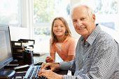 foto of 70-year-old  - Senior man and granddaughter using computer - JPG