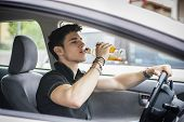 picture of alcoholic drinks  - Young handsome man driving his car while drinking alcohol in the traffic