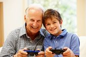 Постер, плакат: Grandfather and grandson playing computer games