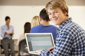 stock photo of 16 year old  - Teenage boy using laptop in class - JPG