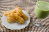 picture of dessert plate  - Snack and Dessert Chinese Traditional Snacks Deep Fried Doughstick on A White Plate Served with Green Tea Soybean Milk - JPG