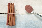 foto of cinnamon  - Some cinnamon sticks tied with a natural rope - JPG