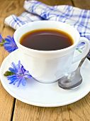 stock photo of chicory  - Chicory drink in a white cup with a spoon and a flower on a saucer, a blue checkered cloth on a wooden board