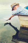 stock photo of old boat  - Boy with paper ship in old boat - JPG