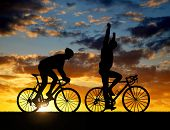 picture of exercise bike  - silhouette of two cyclists riding a road bike at sunset - JPG