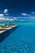image of infinity  - Infinity swimming pool on the beach of tropical island with white beach umbrellas and chairs - JPG