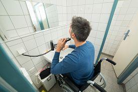 stock photo of wheelchair  - Disabled Man On Wheelchair Trimming Beard In Bathroom - JPG